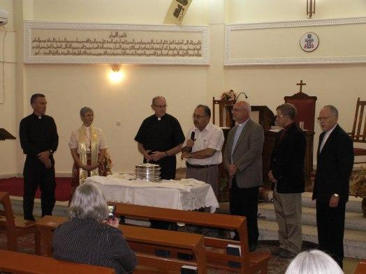 Mark Mueller, Elmarie Parker, Rob Weingartner, Elder Zuhair, Marshall Zieman, Tom Boone and Larry Richards offer communion at the Evangelical Church of Basrah, November, 2012.
