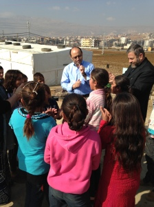 Assis Fadi, moderator of the National Evangelical Synod of Syria and Lebanon encourages the children to sing and dance at an even larger refugee camp near Zahle, Lebanon, in January, 2014.