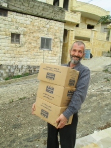 Bassam, the veterinarian from Qusayr, helps unload the truck for the food parcels.