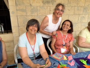 Flanked by Rev. Kate Kotfila of Cambridge, New York, and my new friend Mahsen, from Hasakeh, Syria, we fold peace cranes together.
